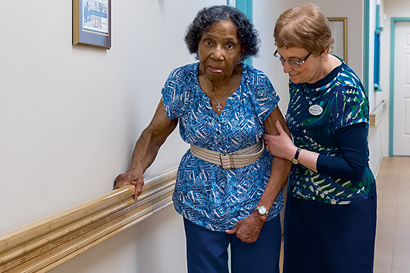 Sheila Selznick helps Mary Francis Mathiews stay ambulatory with short daily walks through the halls of Circle Center Adult Day Services.